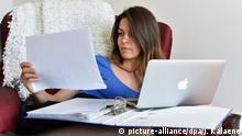 Frau Arbeit mit Laptop und Papier