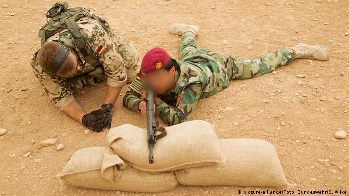German soldier training a Kurdish peshmerga fighter to use a G3 assault rifle.