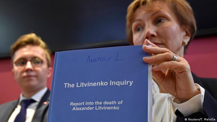 The widow of Alexander Litvinenko holding up an inquiry report into his death