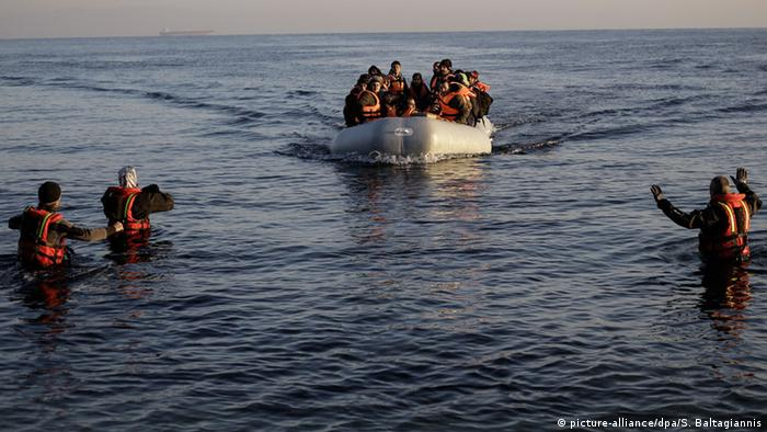 Volunteers signal to a rubber dinghy boat full of refugees and coming from Turkey to Lesvos island, Greece.