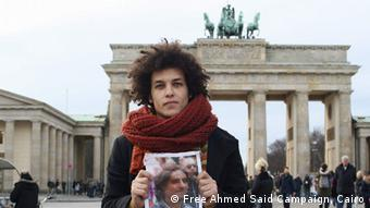 a man holding a poster in front Brandenburg Gate Copyright: Free Ahmed Said Campaign, Cairo