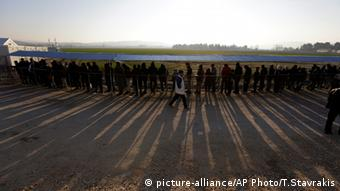 A long line of refugees cast long shadows as they wait for Food in Macedonia.