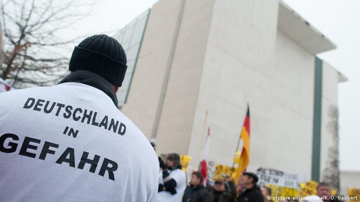 Участник акции в Берлине в футболке с надписью Германия в опасности
