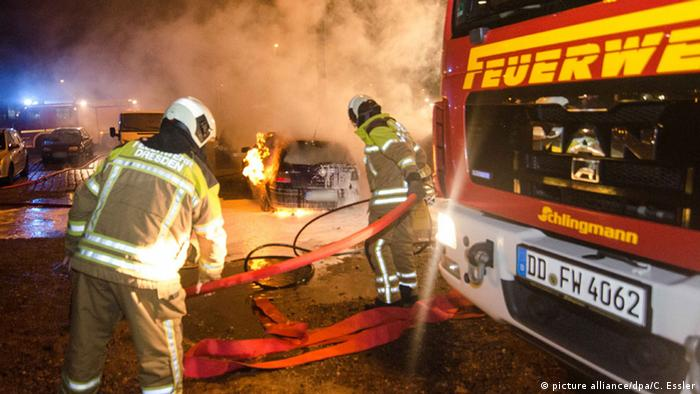 Firefighters attend to burnt out cars in Dresden, Germany