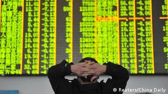 Акционер перед табло с курсами китайских акций