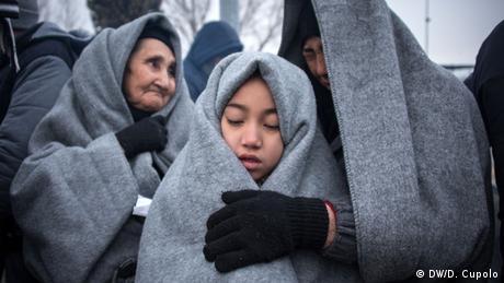 Migrants wrapped in grey felt blankets
