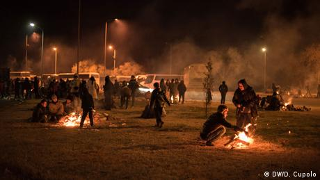 Migrants mull around and tend fires after nightfall at a Greek gas station
