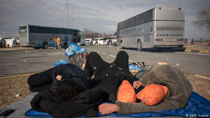 Three men lay on blankets on the ground at a rest area