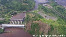 Bildunterschrift:Aerial view taken on December 16, 2013 in Inga shows Inga 1 (rear) and Inga 2 (front) power plants on the Congo river. The Democratic Republic of Congo and South Africa vowed on October 16, 2015 to step up work on a massive new hydroelectric dam on the Congo River that could provide power to the entire continent. The Inga 3 Basse Chute project near Matadi would divert Congo River waters into a 12-kilometre (7.5-mile) channel and then pass them through a 100-metre-high (330-foot) hydropower dam in the Bundi Valley before releasing the water back into the river. The intake would be above the existing Inga 1 and Inga 2 dams, and the outflow downstream from both. AFP PHOTO/MARC JOURDIER (Photo credit should read MARC JOURDIER/AFP/Getty Images)