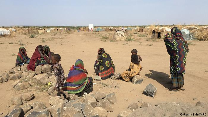 Residents of Asubuli village sit outside in Ethiopia's Somali Region.