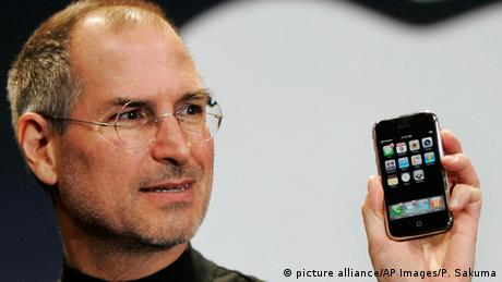 Steve Jobs holding an Apple iPhone (picture alliance/AP Images/P. Sakuma)