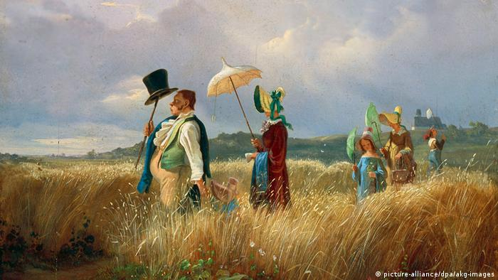 """Das Gemälde """"Der Sonntagsspaziergang"""" von Carl Spitzweg, das eine Familie zeigt, die im Sonntagsstaat hintereinander auf einem von hohem Gras bewachsenen Weg spazieren geht: das Familienoberhaupt, seine Frau, ein Mädchen und eine andere Frau. Er trägt seinen Hut auf einem Stock zum Sonnenschutz, die anderen drei tragen Schirme."""
