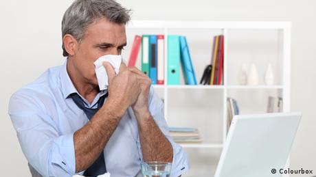 Erkältung Büro Mann mit Taschentuch Nase putzen
