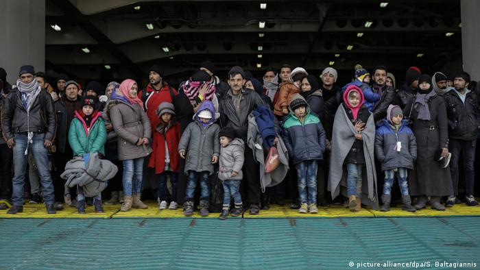Migrants at the port of Piraeus wait to disembark from a ferry
