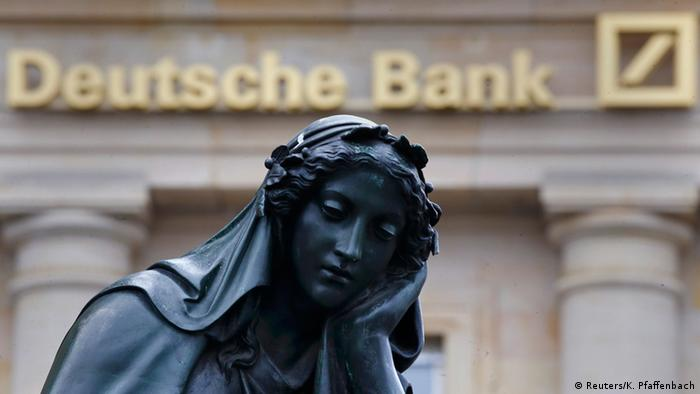 Deutsche Bank sign, with a statue of a woman in the foreground looking sad. (Reuters/K. Pfaffenbach)