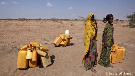women wait in the desert with water canisters