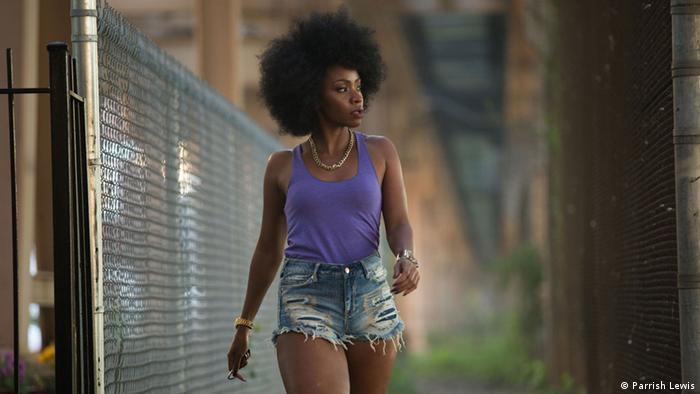 Film still 'Chi-Raq': Teyonah Parris waking along a fence.