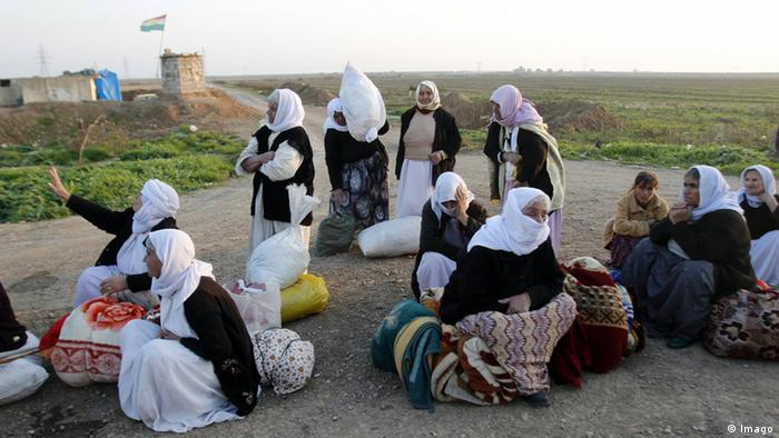 Yazidi women released by IS stand and sit on the ground