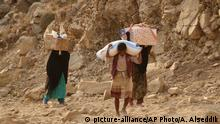 Jan. 17, 2016, In this photo taken on Sunday, Jan. 17, 2016, Yemenis carry relief supplies as they walk along a path after Shiite rebels, known as Houthis besieging the city of Taiz, Yemen. Residents have been going hungry for weeks, the WFP said. (AP Photo/Abdulnasser Alseddik) (c) picture-alliance/AP Photo/A. Alseddik