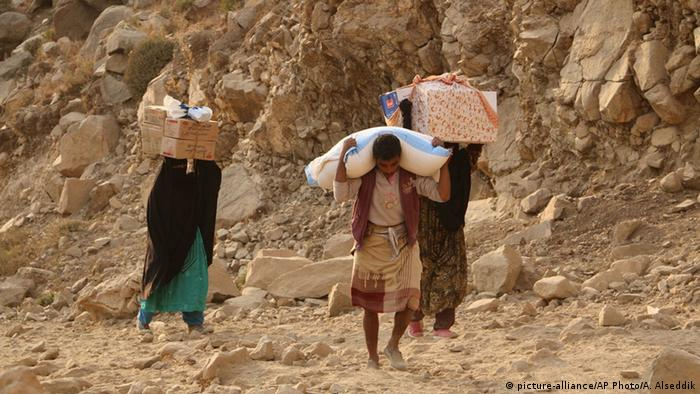 Yemenis carry relief supplies as they walk along a path after Shiite rebels (c) picture-alliance/AP Photo/A. Alseddik