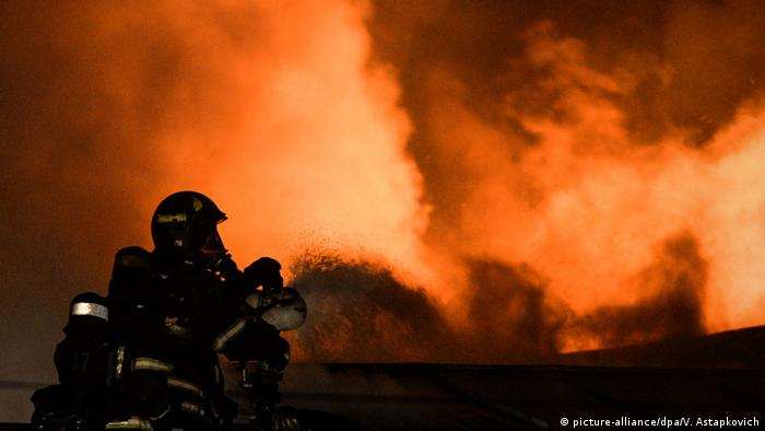 Сотрудник МЧС тушит пожар
