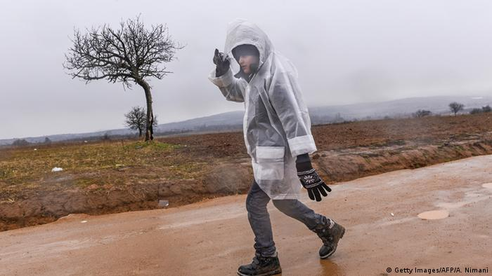 A boy wearing a raincoat walks on a muddy road after crossing the Macedonian border