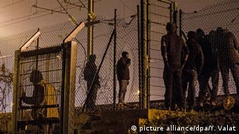 Migrants wait alongside the railway as they try to catch a train to reach England
