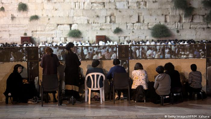 Women sit in the women's area at the Western Wall