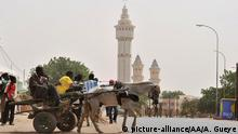February 23, 2012 a man rides a cart near the grand mosque in Touba, a city in the central region of Senegal which is holy for the Mourides, the Sufi Muslim brotherhood to which Senegal President Abdoulaye Wade belongs, on February 23, 2012, ahead of the February 26 Senegalese presidential election. Senegal readied today for a day of rallies and protests wrapping up a presidential election campaign marked by violence over incumbent Abdoulaye Wade's contentious candidacy for a third term in office. AFP PHOTO/ ISSOUF SANOGO (Photo credit should read ISSOUF SANOGO/AFP/Getty Images) came together from all over the world. Achoura Gueye / Anadolu Agency (c) picture-alliance/AA/A. Gueye