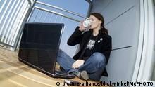 junge Frau sitzt auf einem sonnigen Balkon mit Notebook und trinkt eine Tasse Kaffee | young woman sitting on sunny balcony with laptop and mobile, drinking coffee