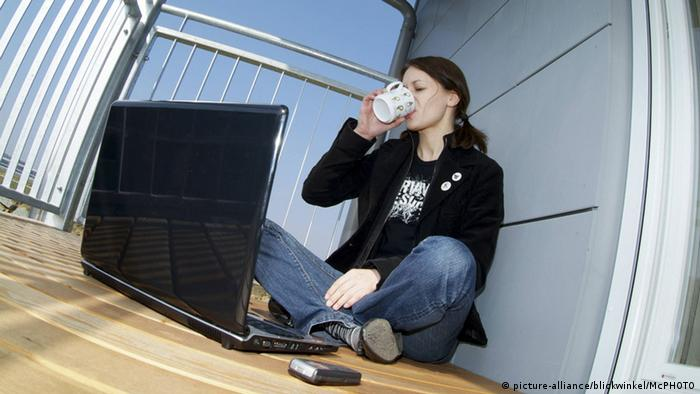 Woman working on her balcony (picture-alliance/blickwinkel/McPHOTO)