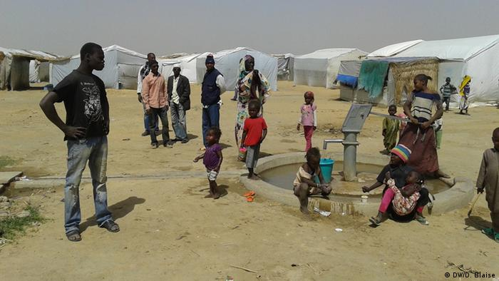 people standing around a well in refugee camp