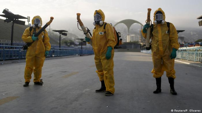 Municipal workers wait before spraying insecticide at Sambodrome in Rio de Janeiro, Brazil