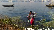 This photo taken on March 19, 2015 shows a Bangladeshi woman collecting contaminated water, to be put over produce at a vegetable market, from the polluted Buriganga in Dhaka. A new UN report launched in New Delhi on March 20 ahead of World Water Day on March 22 warned of an urgent need to manage the world's water more sustainably and highlight the problem of groundwater over-extraction, particularly in India and China. The report says global demand for water is increasing exponentially, driven largely by population growth. AFP PHOTO/ Munir uz ZAMAN (Photo credit should read MUNIR UZ ZAMAN/AFP/Getty Images)