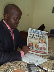 A man holds a copy of the newspaper Mawio (Zuberi Mussa)