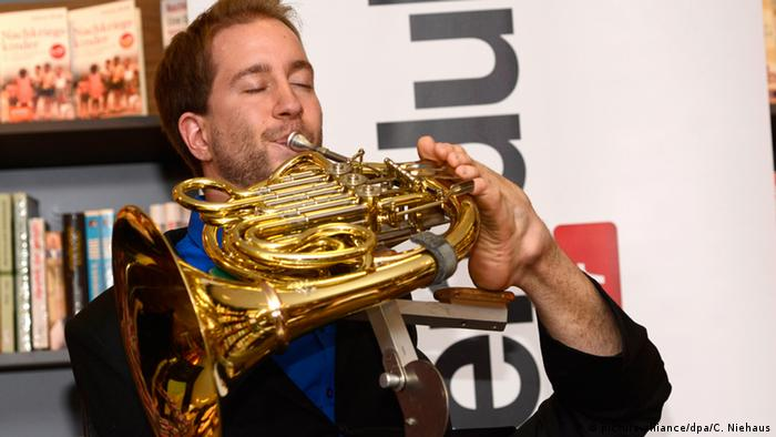 Felix Klieser playing the horn with his foot. Photo: picture-alliance/dpa/C. Niehaus