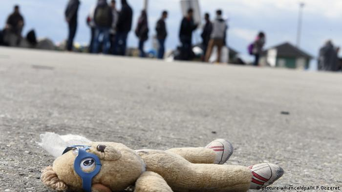 Teddy bear with refugees in the background