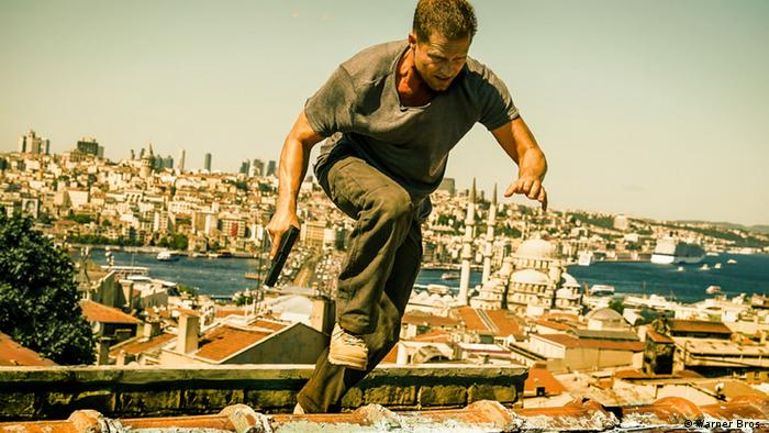 Film scene of Off Duty with Til Schweiger as commissar Tschiller, racing across the roofs of houses (Warner Bros.)