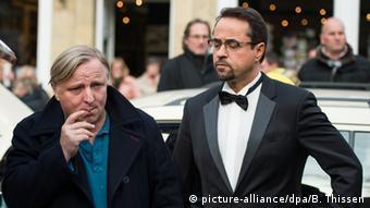 Ein Mann in schwarzem Mantel und Zigarillo steht neben einem Mann mit Brille und Smoking.