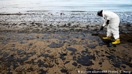 Un hombre vestido con un traje de protección está limpiando la playa contaminada con manchas de petróleo.