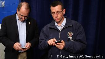 two men holding cell phones Photo by Chip Somodevilla/Getty Images
