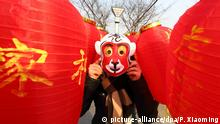 2.2.2016 *** A tourist wearing a monkey mask poses among red lanterns for the upcoming Chinese Lunar New Year, also known as Spring Festival, in Wuxi city, east China's Jiangsu province, 2 February 2016. Copyright: picture-alliance/dpa/P. Xiaoming