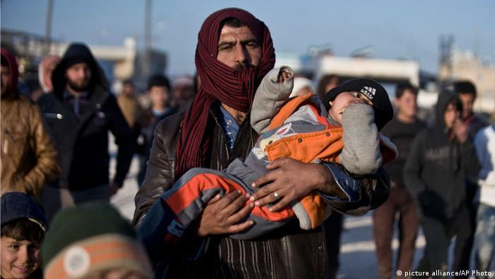 Сириец несет ребенка - беженцы идут к турецкой границе