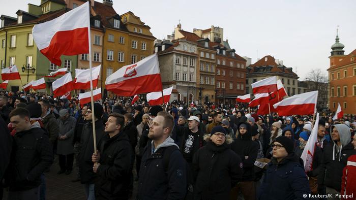 Manifestantes seguram bandeiras da Polônia em protesto anti-imigrantes em Varsóvia, em 2016