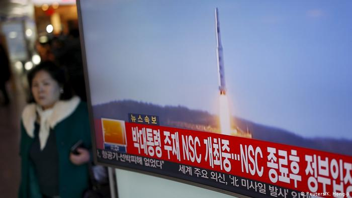 A person walks past a TV screen broadcasting a news report on North Korea's long range rocket launch