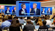 06.02.2016 *** Republican U.S. presidential candidate businessman Donald Trump (R) puts his finger in front of his mouth and tells former Governor Jeb Bush (L) to be quiet as journalists watch the debate on monitors in the media filing center during the Republican U.S. presidential candidates debate sponsored by ABC News at Saint Anselm College in Manchester, New Hampshire February 6, 2016. REUTERS/Rick Wilking © Reuters/R. Wilking