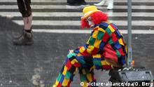 04.02.2008 *** Ein Karnevalist im Clownskostüm sitzt am Montag (04.02.2008) in Köln im Regen am Straßenrand. Mit dem Rosenmontagsumzug erreicht der Karneval im Rheinland seinen Höhepunkt. (Foto durch Glasscheibe) Foto: Oliver Berg dpa/lnw +++(c) dpa - Bildfunk+++ Copyright: picture-alliance/dpa/O. Berg