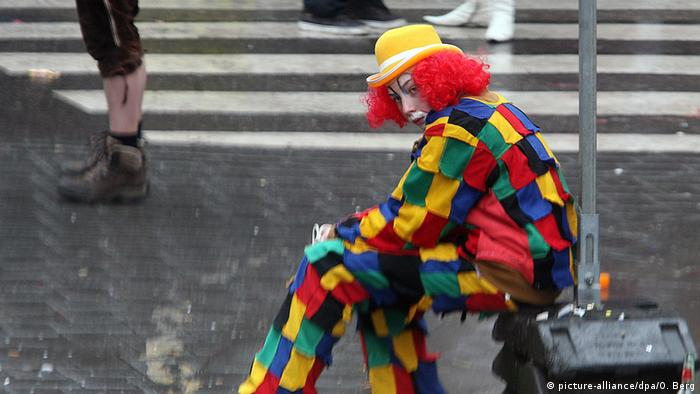Carnival clown sat in bad weather