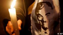 A Lebanese supporter of Lebanon's slain former Prime Minister Rafik Hariri wears a scarf with a picture of Hariri while holding a candle, a day ahead of the first anniversary of his assassination, during a sit-in, near the bombing site, in Beirut, Lebanon, Monday, Feb. 13, 2006. Lebanon will mark on Tuesday, Feb. 14, the first anniversary of the assassination of Hariri, who was killed along with 20 other people in a massive bombing. Anti-Syrian Lebanese groups have blamed Syria for Hariri's assassination. Syria has denied involvement in the killing. (AP Photo/Hussein Malla)