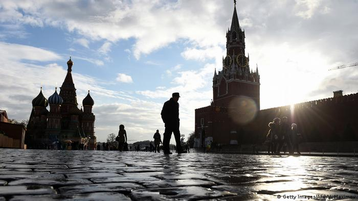 People walk across Red Square, with the Kremlin's Spasskaya (Saviour) Tower (R) and St. Basil's Cathedral (L) seen in the background (C): Getty Images/AFP/V. Maximov